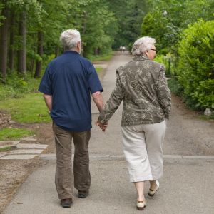 Old-couple-walking-outdoors-on-path-near-tree1
